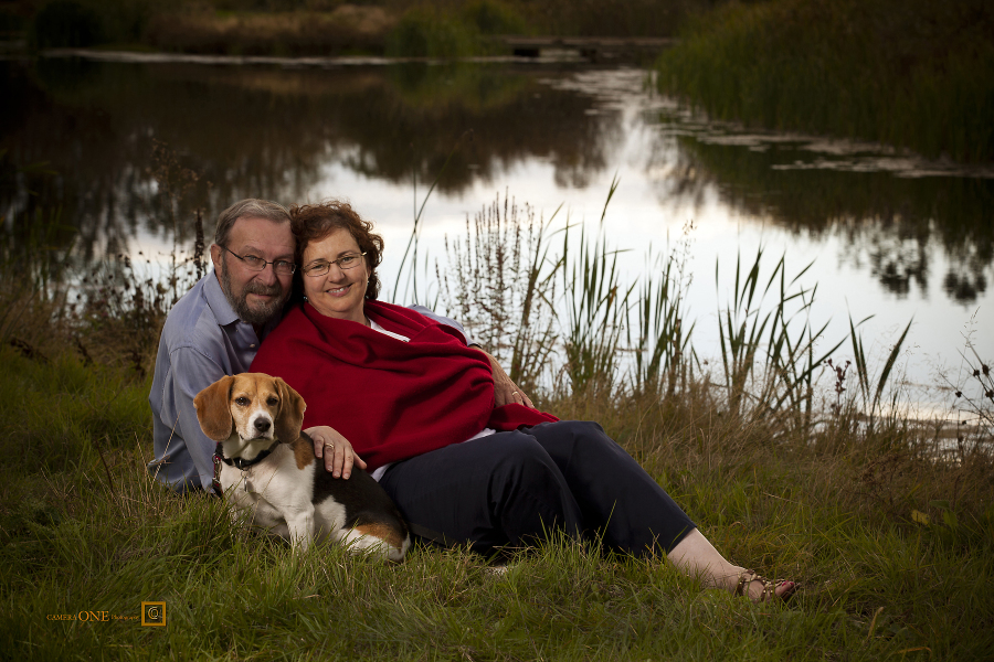 A couple's photo with their dog beside a lake