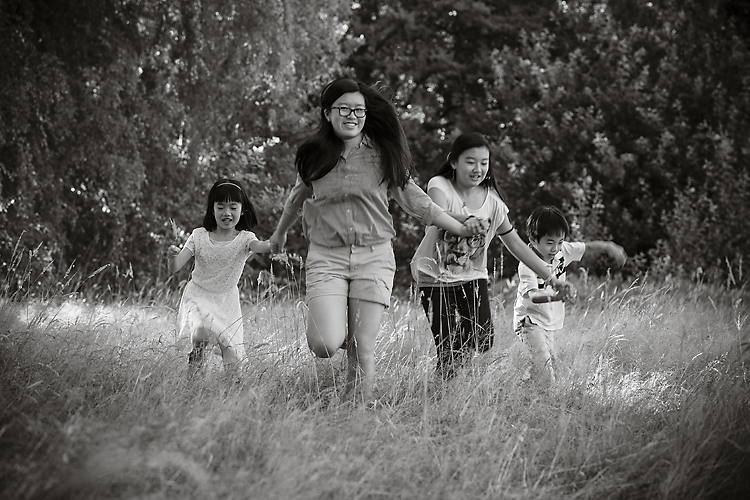 Cousins running in grassy field